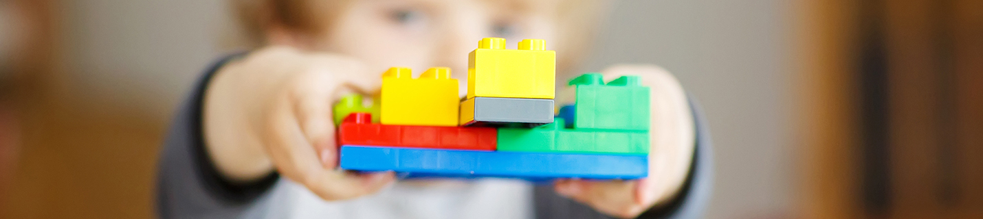 Happy little kid boy playing with construction blocks with creat